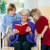 Grandmother Reading Book to Grand Children. Grandmother sitting in chair Reading Book to two Grand Children Royalty Free Stock Images