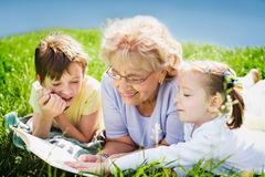 Grandmother reading book to grandchildren. Outdoors Stock Photography