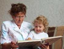 Grandmother reading book to the granddaughter Stock Photos