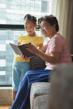 Grandmother reading book to her granddaughter Stock Image