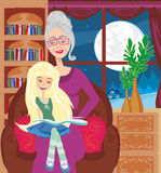 Grandmother is reading a book to her granddaughter Royalty Free Stock Photo