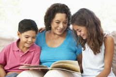Grandmother Reading With Grandchildren. At Home Together Royalty Free Stock Images