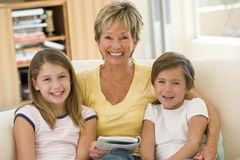 Grandmother reading with grandchildren. Indoors Royalty Free Stock Photos