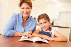 Grandmother Reading With Granddaughter At Home Stock Photography
