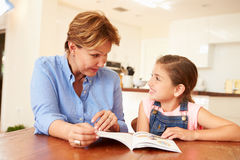 Grandmother Reading With Granddaughter At Home Stock Photos