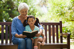 Grandmother reading novel to granddaughter sitting on wooden bench Royalty Free Stock Photo