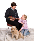 Grandmother reading a novel to her granddaughter Stock Photography