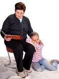 Grandmother reading a novel to her granddaughter Royalty Free Stock Image