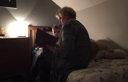 Grandmother reading to grandchild. Grandmother reading bedtime story to grandson in his bedroom stock photos