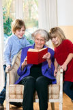 Grandmother reading to her grandchildren. Grandmother reading to her two cute young blond grandchildren as she sits in a comfortable armchair with them leaning Royalty Free Stock Photography