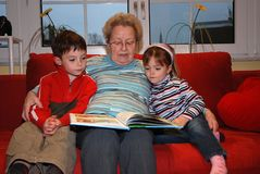 Grandmother reads aloud with her grandchildren. Great grandma sitting with her grandchildren in her arms on a red couch, reading a book and looking the pictures stock photos