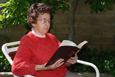 Grandmother Reads Bible. Grandmother reads words of comfort from the Bible while sitting in her garden Stock Photos