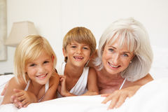 Grandmother Relaxing On Bed With Grandchildren. Smiling At Camera Royalty Free Stock Images