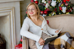 Grandmother relaxing on a sofa in front of the family Christmas Stock Image