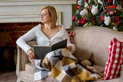 Grandmother relaxing on a sofa in front of the family Christmas Royalty Free Stock Image