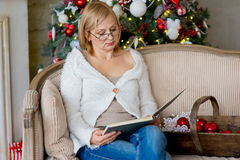 Grandmother relaxing on a sofa in front of the family Christmas Royalty Free Stock Images