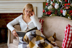 Grandmother relaxing on a sofa in front of the family Christmas Stock Photos