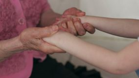 Wrinkled hands of an old grandma hold arms a child stock video