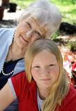 Grandmother's Love. A pretty blond girl and her grandmother in the garden.  The little girl looks serious.  Vertical view Royalty Free Stock Photography