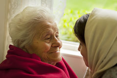 A Grandmother's Love. An elderly women smiling at her granddaughter stock photography
