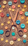 Grandmother's set. Old scissors and a scattering of multi-colored buttons Royalty Free Stock Images