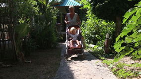 Grandmother seats blonde toddler into pram  near house. Grandmother seats blonde girl toddler into pram and fasten belts near house among tropical plants stock footage