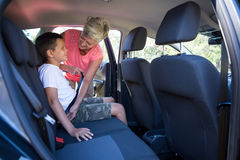 Grandmother securing her grandson with seat belt. In a car Stock Photo