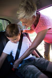 Grandmother securing her grandson with seat belt. In a car Stock Image