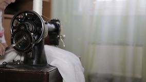 Grandmother sews clothes on an old sewing machine stock video