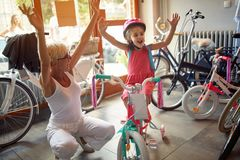 Grandmother shopping new bicycle for little girl. Happy grandmother shopping new bicycle for little girl royalty free stock image