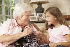 Grandmother Showing Granddaughter How To Knit At Home Stock Images