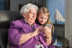 Grandmother showing her grandchild something funny on her smartphone. A 95 year old women is holding a smartphone and showing her grandchild something funny. She stock image