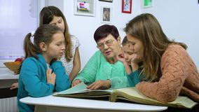 Grandmother showing old photo album to her four granddaughters. Senior woman showing black and white photos to children. Family, relationship and communication stock video
