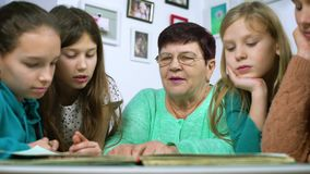 Grandmother showing old photo album to her four granddaughters. Senior woman showing black and white photos to children. Family, relationship and communication stock footage