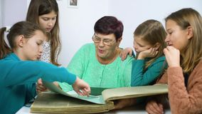 Grandmother showing old photo album to her four granddaughters. Senior woman showing black and white photos to children. Family, relationship and communication stock video footage