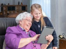 Grandmother showing something funny to her grandchild on her tab. A 95-year-old women is holding a tablet and showing something funny to her grandson. She is royalty free stock image