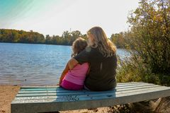 Grandmother sits with her granddaughter as they enjoy nature outside sitting on a bench royalty free stock images