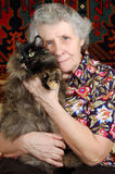 Grandmother sitting with cat on her hands. Near head Royalty Free Stock Photos