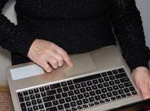 Grandmother sitting at the laptop. Stares stock photo