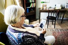 Grandmother sitting and looking at her husband`s photo Stock Photos