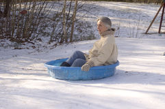 Grandmother sliding in kiddie pool. Grandmother sliding down a hill in a plastic children's swimming pool Royalty Free Stock Photo