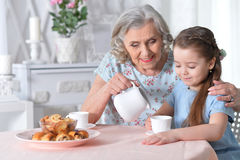 Grandmother with a small granddaughter drinking tea. Happy grandmother with a small granddaughter drinking tea Royalty Free Stock Photography