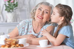 Grandmother with a small granddaughter drinking tea. Happy grandmother with a small granddaughter drinking tea Royalty Free Stock Photos