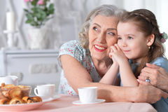 Grandmother with a small granddaughter drinking tea. Happy grandmother with a small granddaughter drinking tea Stock Images