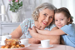 Grandmother with a small granddaughter drinking tea. Happy grandmother with a small granddaughter drinking tea Royalty Free Stock Images