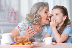 Grandmother with a small granddaughter drinking tea. Happy grandmother with a small granddaughter drinking tea Stock Photography