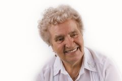 Grandmother smiling. Elderly female against the white background Royalty Free Stock Images