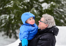 Grandmother Smiling at Grandson Outside in Winter Stock Photography
