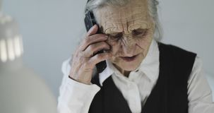 Grandmother speaking on the mobile phone indoors. An old woman with deep wrinkles uses a new phone in the office stock video footage