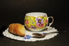Grandmother still life. Cup, spoon and pie on white round serviette, dark background Stock Photo